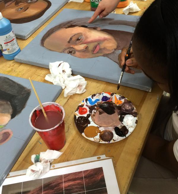 Student Cori Gordon works on her portrait of fellow student Josayra Mateo.