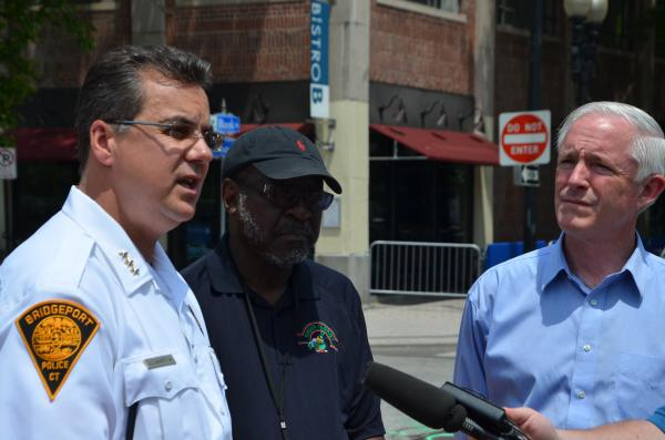 """Police Chief Joseph Gaudett, Councilman James Holloway, and Mayor Bill Finch announce the pilot """"crosswalk flag"""" program at 999 Broad Street in Bridgeport. If the project is successful, Holloway said Bridgeport would expand it to eight other crosswalks in the city."""
