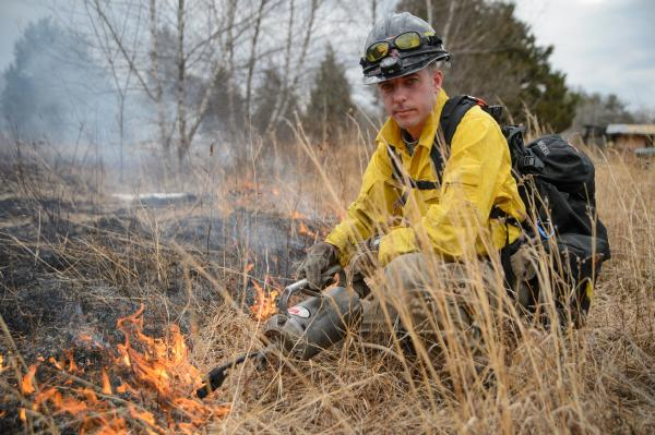 Chris Renshaw with a drip torch as he fights a wildfire.