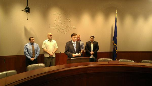 Senator Chris Murphy discusses a report from the Health, Education, Labor, and Pensions Committee at the state capitol in Hartford with veterans.