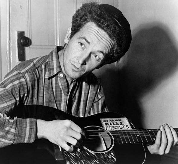 Woody Guthrie performing with his famous guitar.