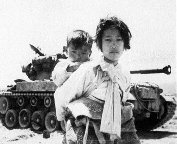 A girl carries her brother on her back, during the Korean War, June 9, 1951.