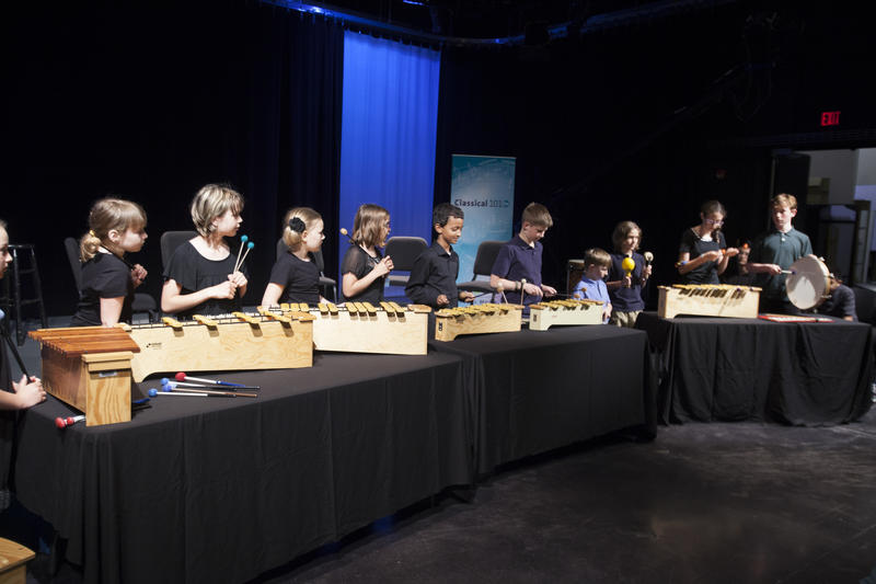 color photo of eleven children playing glockenspiel-like instruments beore a black and blue backdrop