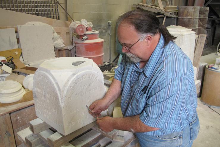 Mel Lee of Columbus Art Memorial restores a gravestone from 1876.
