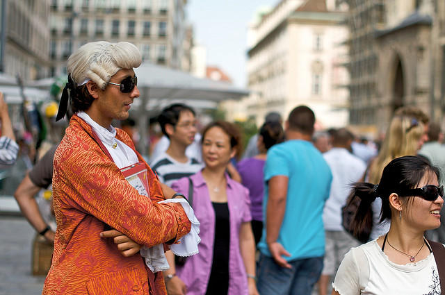 color photograph of a man dressed like Mozart and wearing modern-day sunglasses while outside in a crowded street