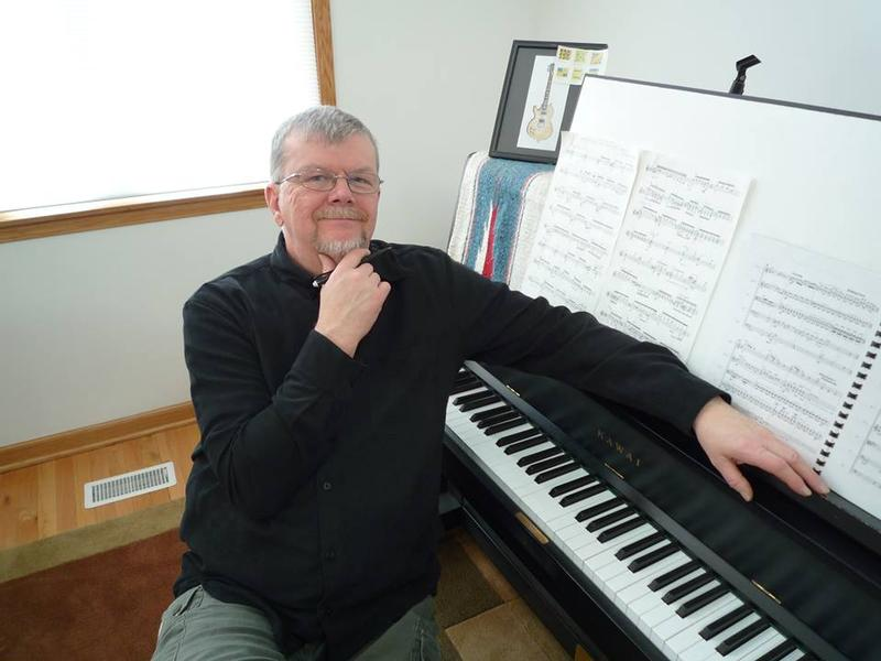 photo of Richard Smoot sitting at piano with music scores on the ledger