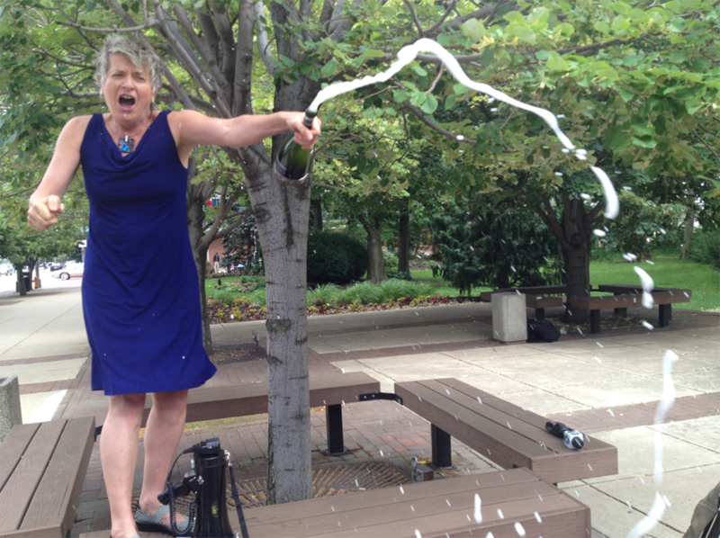 Equality Ohio Executive Director Elyzabeth Holdford celebrates Supreme Court ruling by popping open a bottle of champagne near the Franklin County Courthouse.