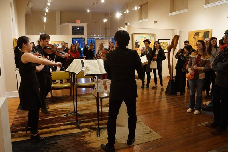 color photograph of two violiists and a violist standing up in an art gallery and playing their instruments