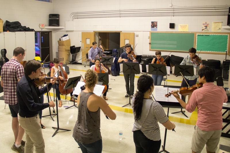 color photo of eleven string players rehearsing in a classroom