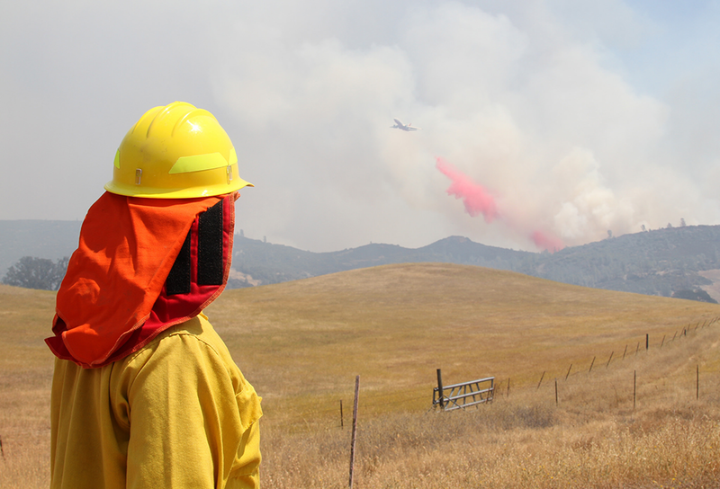 A firefighter watches a helicopter fight a wildfire in Califonia.