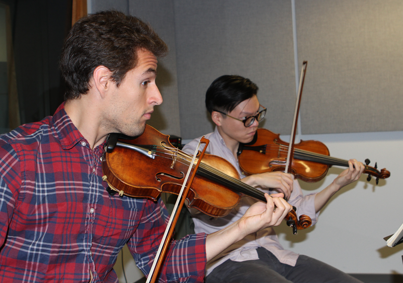 Dover Quartet violinists Joel Link (left) and Bryan Lee playing their instruments.