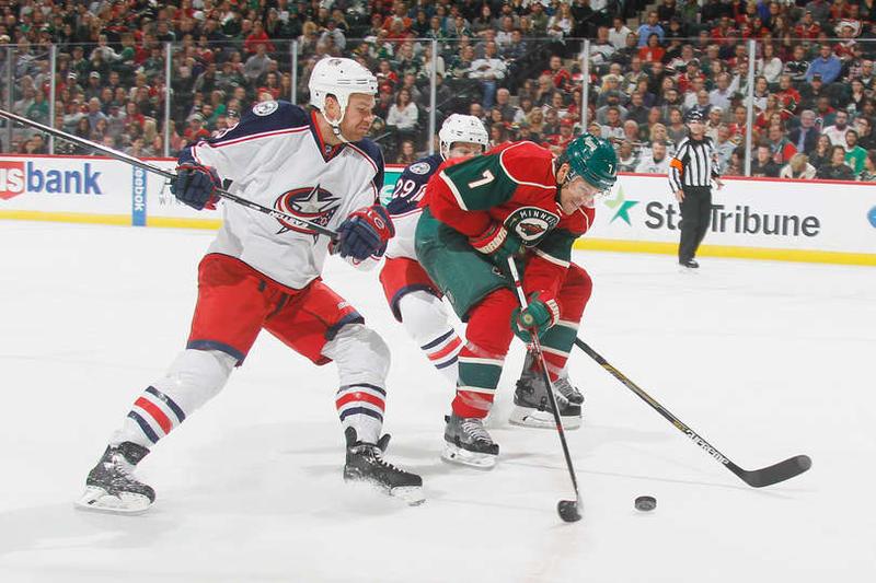 The Minnesota Wild's Chris Porter skates around Columbus' David Clarkson and Cody Goloubef.