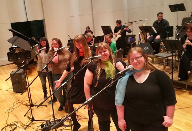 color photograph of members of the Reno Video Game Symphony standing onstage and near microphones