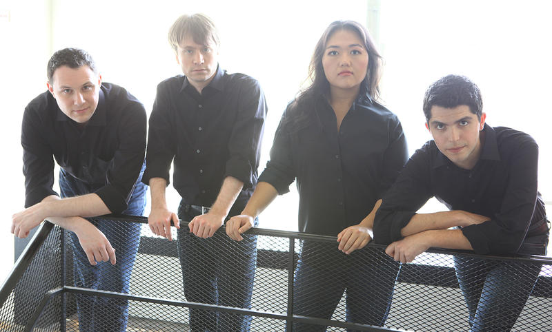 color photograph of the members of the Calidore String Quartet standing in a row wearing jeans and black shirts