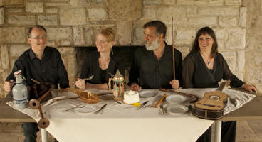 olor photograph of members of the Early Interval sitting at a medieval-style feasting table
