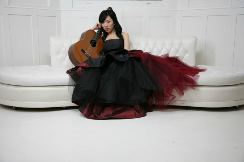 color photograph of Xuefei Yang reclining with her guitar