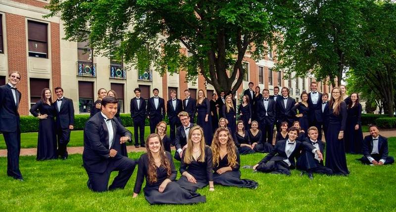 color photo of members of the Bexley HS Vocal Ensemble in concert dress standing and sitting outside Bexley High School