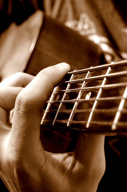 sepia-toned photo of a left hand playing a guitar