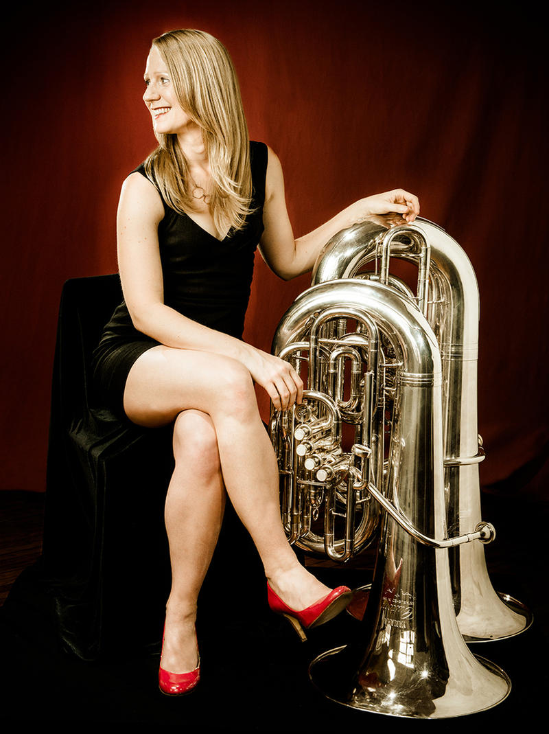 color photograph of Carol Jantsch wearing a short black dress, and sitting next to her tuba