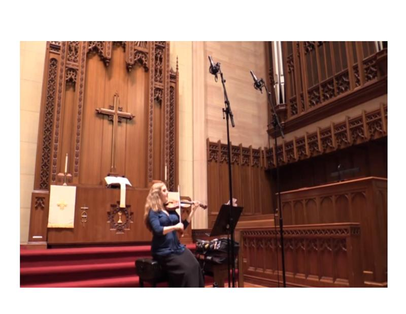 color photo of Rachel Barton Pine sitting down and playing her violin in the chancel area of St. Paul's UCC, Chicago
