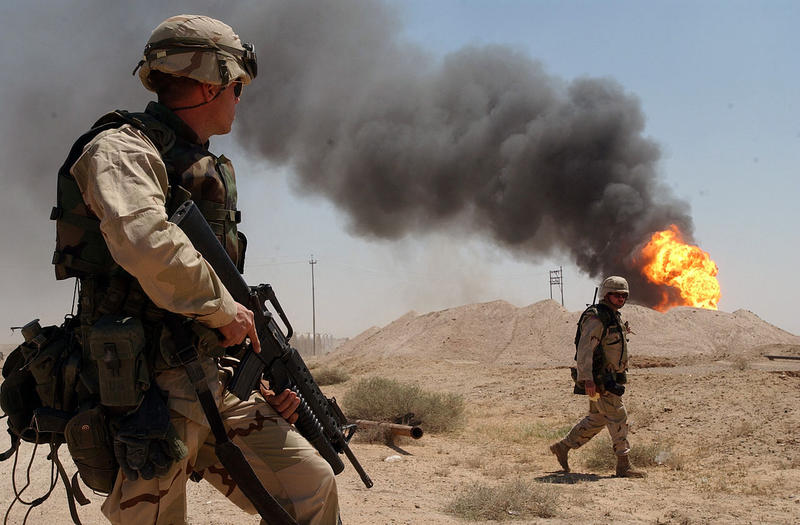 A U.S. soldier stands guard duty near a burning oil well in the Rumaila oil field, Iraq, April 2003