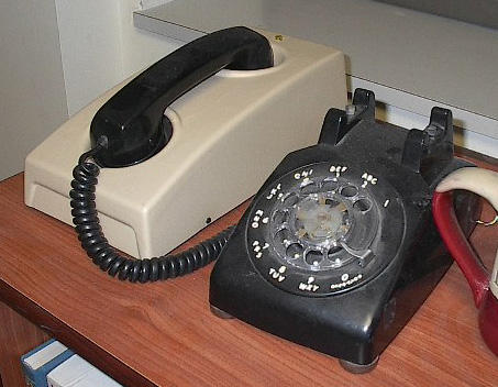 "color image of a black ol-styl phone wiht handset resting in a white modem ""cradle."""
