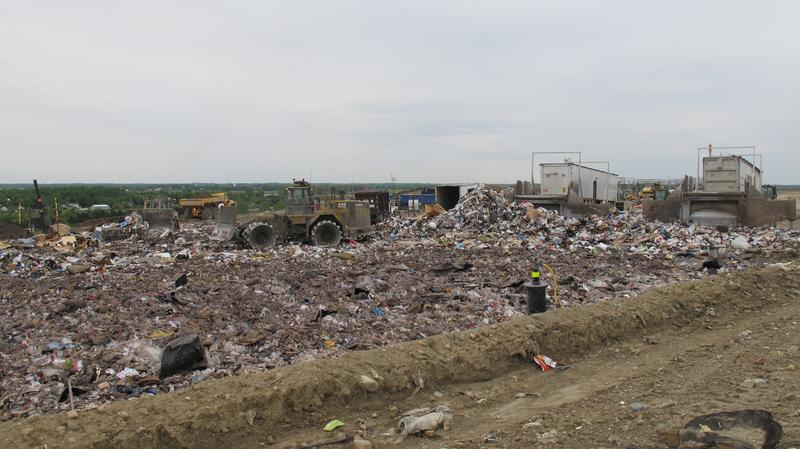 Trucks work at the face of the landfill to make sure all the trash gets filled in properly and evenly.