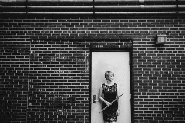 black-and-white photo of Lindsey Goodman holding her flute and standing infront of a light-colored door in an exterior brick wall