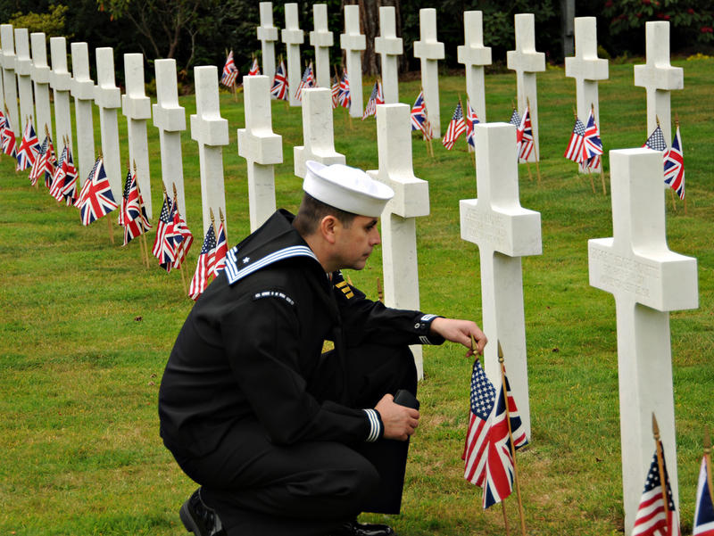 A sailor pays his respects to a fallen service member buried at the Brookwood American Cemetery and Memorial in Brookwood, England.