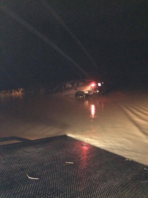 A tow truck pulls a car out of flood waters in northern Union County.