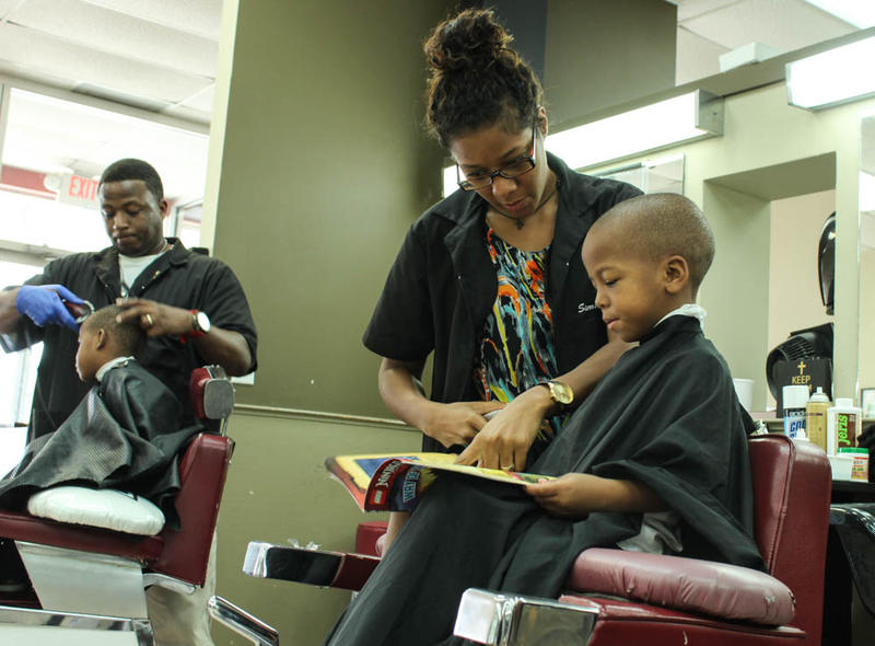 Four-year-old Deongre Coley flips through a Legos book with his barber, a student at the Ohio State College of Barber and Styling.