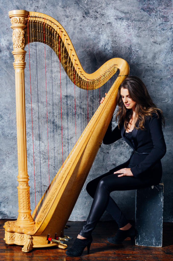 color photograph of Bridget Kibbey wearing black sitting at her harp