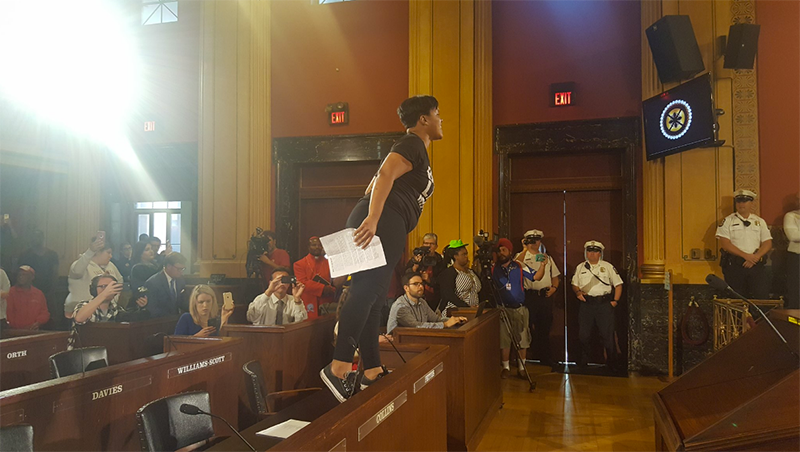 A protester disrupts Columbus City Council's meeting on Monday calling for an independent investigation of the fatal police shooting of Tyre King.