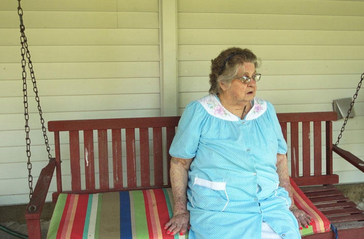 A Cheshire, Ohio resident sits on her porch to talk about the buyout of the town.