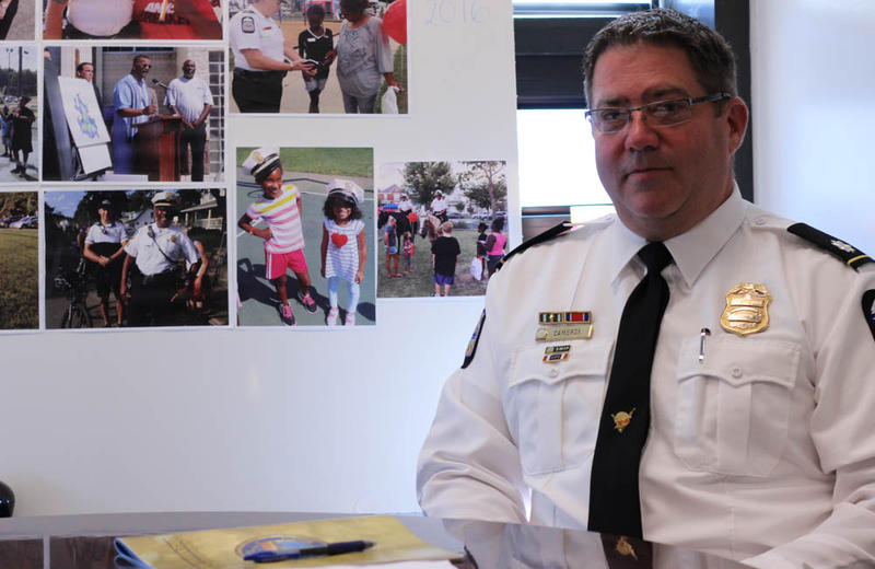 Commander Gary Cameron creates the annual report on the Community Safety Initiative. Behind him are photos from the thousands of positive interactions he says police shared with citizens this summer.