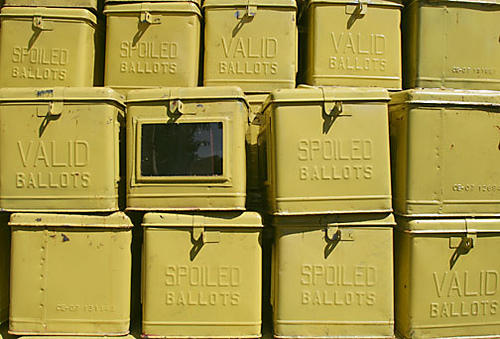 color photo of severl yellow metal ballot boxes stacked on top of each other