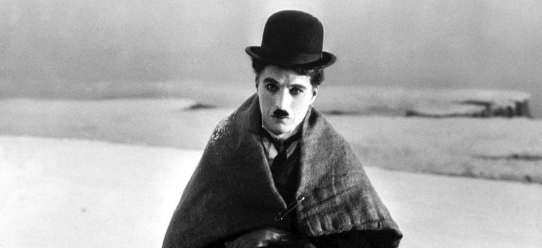 black-and-white still photo of Charlie Chaplin as the Little Tramp and sitting on a snowy landscape in The Gold Rush