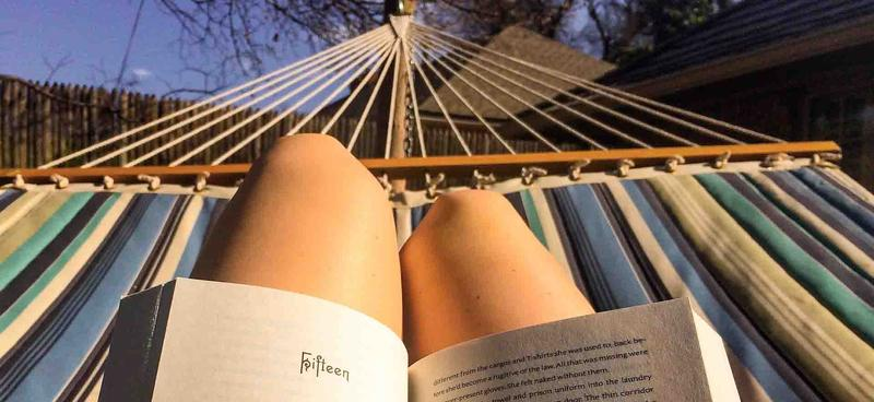 color photo of person reading a book on a hammock