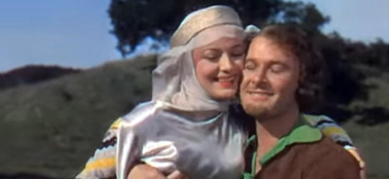 color photo of Olivia de Havilland as Maid Marian and Errol Flynn as Robin Hood in The Adventures of Robin Hood