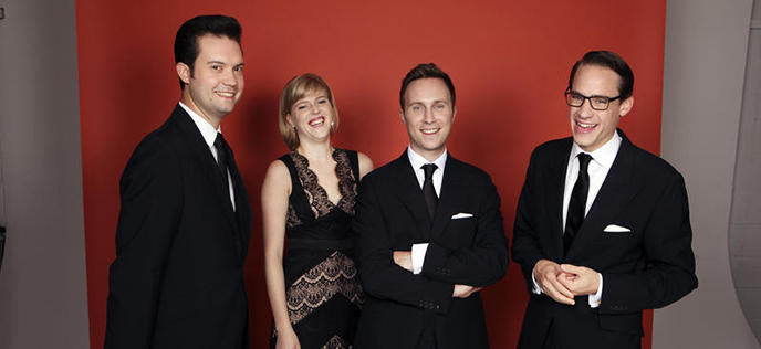 the four members of the Doric String Quartet with a red background