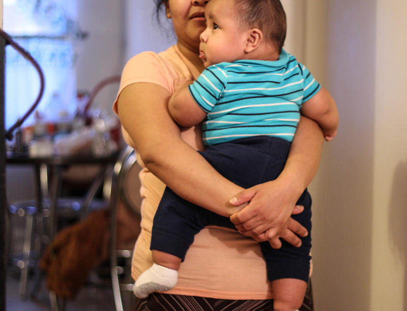 At her home, Perez cradles her four-month old son. Her Husband was recently deported back to Guatemala.