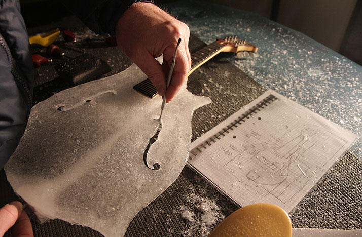 A block of ice is transformed into a working guitar.