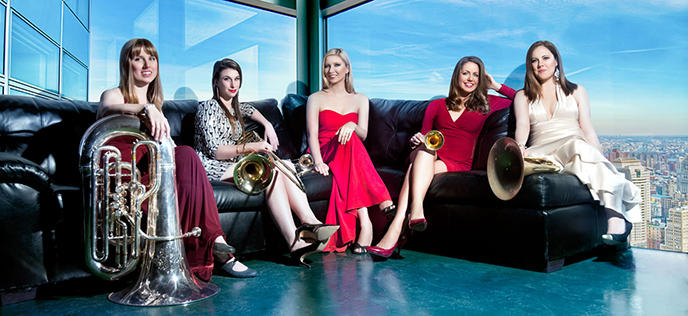 color photo of the members of Seraph Brass dressed up and sitting with their instruments on a sofa