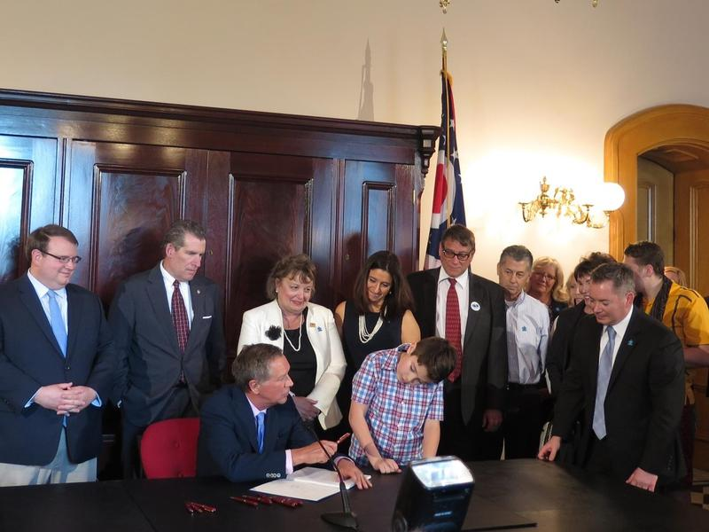 Kasich holds a ceremonial signing of a bill requiring autism treatments.