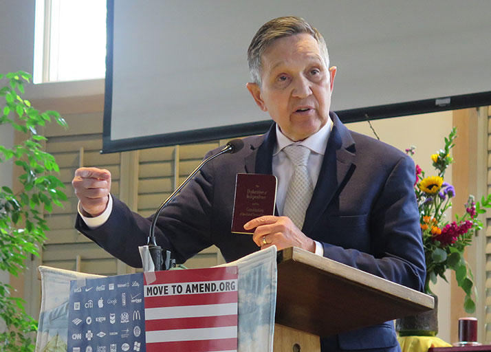 Dennis Kucinich holds his pocket Constitution during a speech at a Columbus church on April 2, 2017.