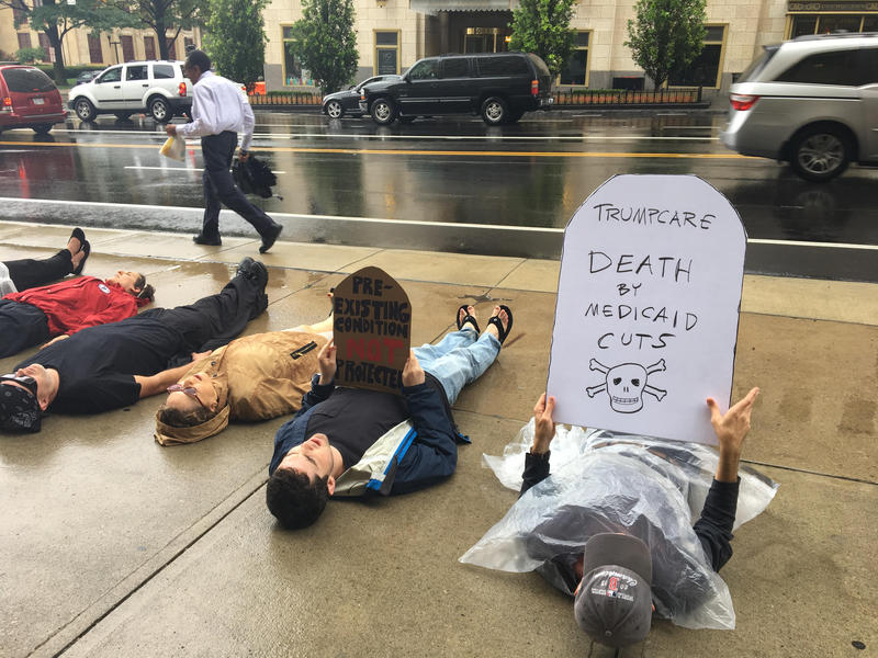 Protestors hold a die-in in front of Senator Rob Portman's office.