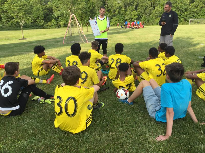 Nearly half of a Columbus Crew youth soccer team is made up of African refugees. They gather around coach Fabio Patterson during halftime.
