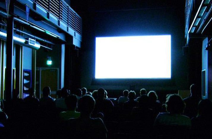 color photo of people sitting in a dark movie theater watching a bright white blank screen