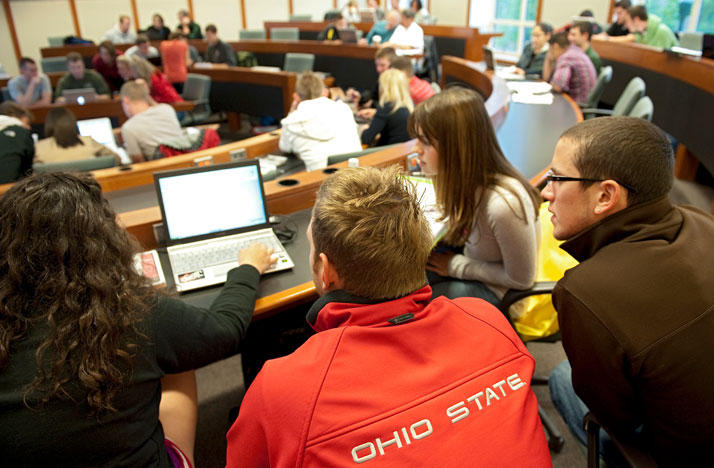 Students gather around a laptop computer in an Ohio State University classroom.