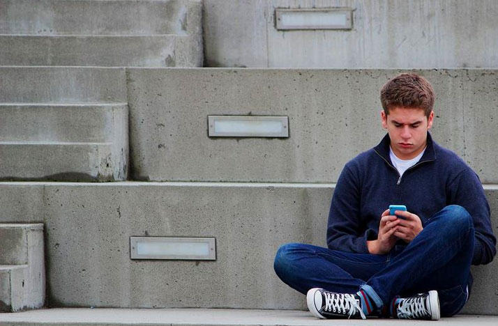 Teen sitting alone using phone.